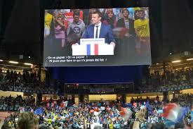 Una manifestazione a sostegno di Macron, con i tricolori francesi mescolati con le bandiere azzurre dell'UE